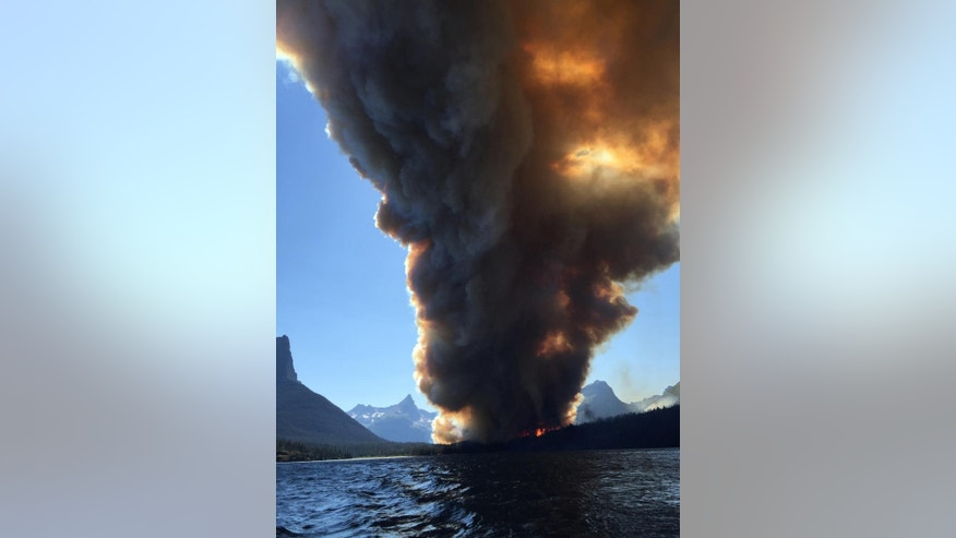 In this photo taken, Tuesday, July 21, 2015, smoke from the Reynolds Creek fire rises above the landscape at St. Mary Lake in Glacier National Park, Mont. State Rep. Jenny Eck, who was hosting a delegation from Australia on a tour of the park, took this photo of the fast-moving wildfire. The flames torched a car and a historic cabin and forced tourists to abandon their vehicles on the park's most popular roadway while officials evacuated hotels, campgrounds and homes. (Jenny Eck via AP)