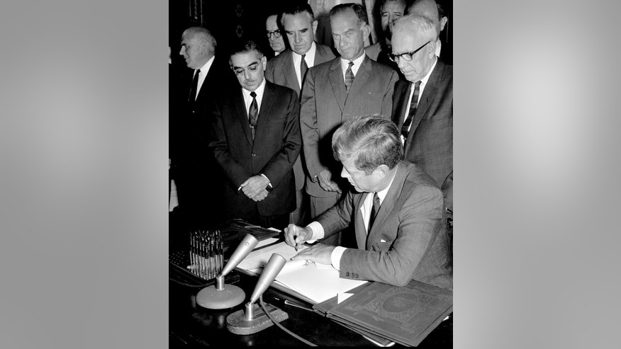 FILE -  In this Oct. 7, 1963, file photo, President John F. Kennedy signs the Limited Test Ban Treaty during a ratification ceremony in the White House Treaty Room in Washington.  Critics of the Iran nuclear deal claim it is flawed, among many reasons, because it does not demand that Tehran also change its behavior at home and abroad. That complaint ignores the United States' long history of striking arms control agreements with the Soviet Union, a far more dangerous enemy. Dating as far back as the Limited Test Ban Treaty in 1963, U.S. administrations engaged the Soviet Union in agreements to limit nuclear threats while not linking deals to Soviet human rights abuses and the active arming and funding of leftist, anti-American revolutionary movements around the world. Watching from left are, Sen. John A. Pastore, D-R.I.; Undersecretary of State W. Averell Harriman; Sen. William Fulbright, D-Ark.; Sen. George Smathers, D-Fla.; Sen. George D. Aiken, R-Vt.  (AP Photo/File)