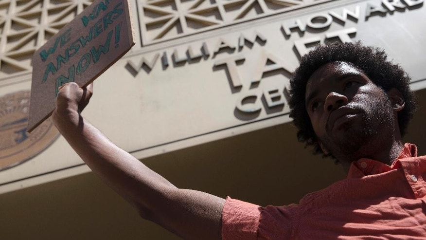 Alexander Shelton, 25, a student at the University of Cincinnati, holds a sign outside the office of Hamilton County prosecutor Joe Deters' office during a protest demanding release of video showing the shooting death of Samuel Dubose by a university police officer, Thursday, July 23, 2015, in Cincinnati. Deters has said he won't release the video until the investigation into Sunday's shooting is complete. (AP Photo/John Minchillo)