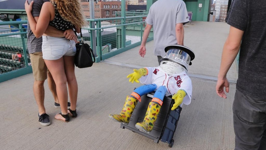 A couple embrace as Dan Winske wheels hitchBOT through the stands before a baseball game at Fenway Park between the Boston Red Sox and Detroit Tigerson Friday, July 24, 2015, in Boston. The robot's hitchhiking journey across the United States took a detour to Fenway. (AP Photo/Charles Krupa)