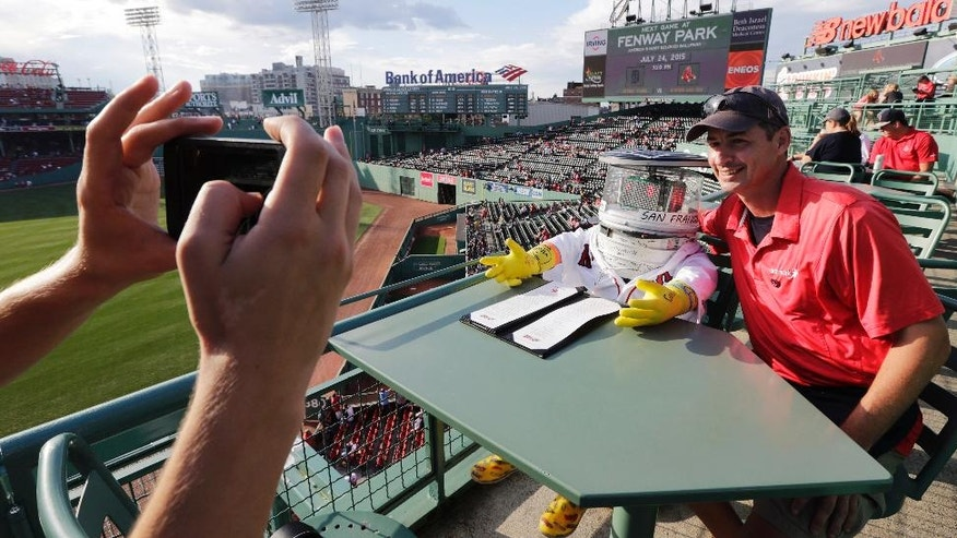 Food service worker Chris Corsi poses with hitchBOT before a baseball game at Fenway Park between the Boston Red Sox and the Detroit Tigers on Friday, July 24, 2015, in Boston. The robot's hitchhiking journey across the United States. took a detour to Fenway. (AP Photo/Charles Krupa)