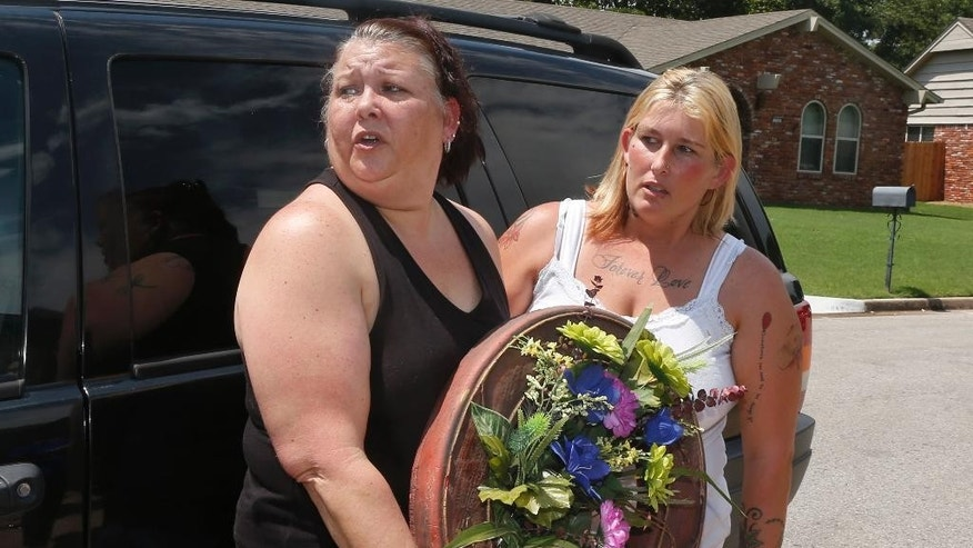 Cindy Rigney, left, and Glenna Parkman, right, who live in Broken Arrow, arrive with a wreath outside of a home in Broken Arrow, Okla., Thursday, July 23, 2015, where five family members were discovered by authorities stabbed to death. The women were turned away by police and told to come back later. (AP Photo/Sue Ogrocki)