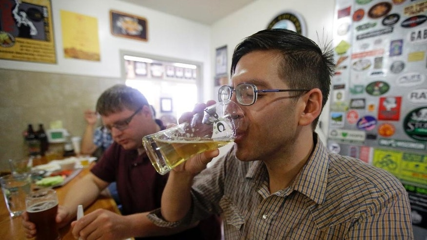 Stephen Baker, left, eats pie while his brother Daniel Baker, drinks a beer at the Epic Brewery during pie and beer day Friday, July 24, 2015, in Salt Lake City. Most people will gathered Friday in Utah to celebrate the state's Mormon heritage at Pioneer Day parades featuring floats, carriages and women in prairie dresses. But many non-Mormons will be enjoying an increasingly popular counter-holiday with a playful name: Pie and Beer Day. (AP Photo/Rick Bowmer)