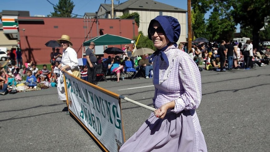 People celebrate the state's Mormon heritage at the Pioneer Day parade Friday, July 24, 2015, in Salt Lake City. The Pioneer Day parade featuring floats, carriages and women in prairie dresses. But many non-Mormons will be enjoying an increasingly popular counter-holiday with a playful name: Pie and Beer Day. (AP Photo/Rick Bowmer)