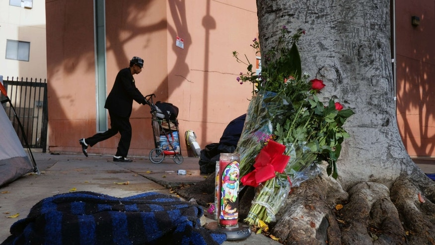March 2, 2015: Photo shows a pedestrian walks past flowers and candles placed on a sidewalk near where Charly Keunang a homeless man was shot and killed by police in the Skid Row section of downtown Los Angeles.