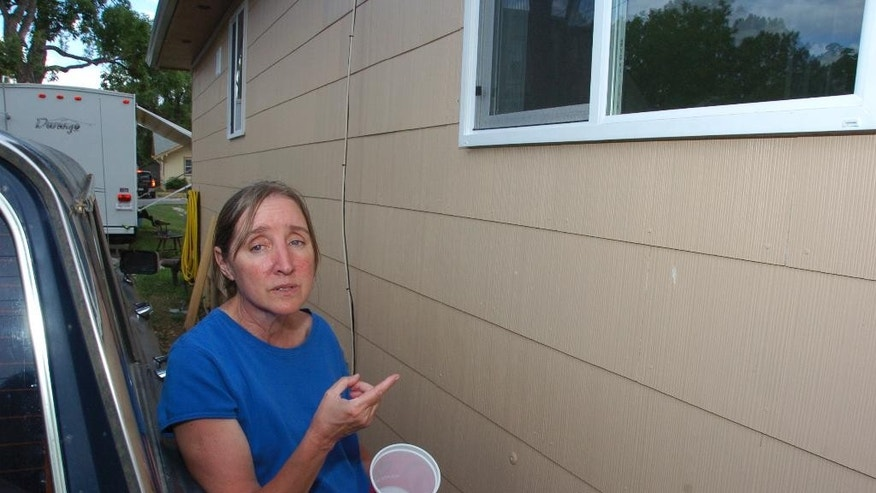 In this Wednesday, July 22, 2015, photo, Regina Culver points to the window of her Billings, Mont., home through which her 17-year-old son shot and killed a friend who was knocking on her son's window late at night. Culver says she doesn't think criminal charges are warranted in a case that prosecutors plan to put before a special coroner's jury. (AP Photo/Matthew Brown)