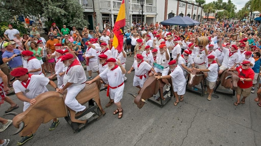 "In this photo provided by the Florida Keys News Bureau, Ernest Hemingway Look-Alikes kick off the annual ""Running of the Bulls"" Saturday, July 25, 2015, in Key West, Fla. The whimsical and much safer answer to the event's namesake in Pamplona, Spain, was staged as a facet of the island city's annual Hemingway Days festival that ends Sunday, July 26. Hemingway lived and wrote in Key West throughout the 1930s. (Andy Newman/Florida Keys News Bureau via AP)"