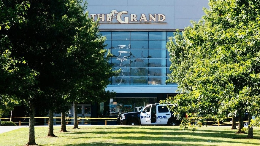 Authorities park at the scene of a Thursday night shooting at The Grand Theatre, in Lafayette, La. on Friday, July 24, 2015. John Russel Houser, 59, stood up about 20 minutes into a movie and fired first at two people sitting in front of him, then aimed his handgun at others, firing at least 13 times, police said Friday. he two fatalities were identified as 33-year-old Jillian Johnson and 21-year-old Mayci Breaux. At least one of the wounded, ranging from their late teens to their late 60s, was in critical condition, Craft said. (AP Photo/Denny Culbert)