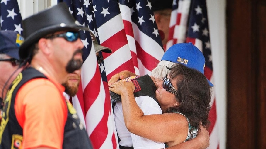 A member of the Patriot Guard Riders at left is embraced by a mourner while standing with an American flag outside the visitation of Lance Cpl. Skip Wells, a Georgia Marine gunned down at a Navy-Marine reserve center in Chattanooga, Tenn., Friday, July 24, 2015, in Kennesaw, Ga. Wells' funeral is scheduled for Sunday followed by the burial at Georgia National Cemetery in Canton. (AP Photo/David Goldman)