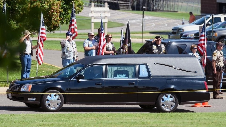 A hearse carrying the remains of Sgt. Carson Holmquist arrives before a public visitation at Grantsburg High School in Grantsburg, Wis., Saturday, July 25, 2015. Holmquist was killed by a gunman in Chattanooga, Tenn. (AP Photo/Craig Lassig)