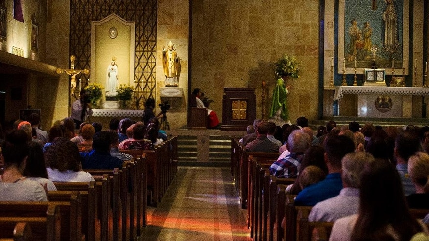 "Parishioners attend church service at Our Lady of Fatima Catholic church to remember and honor the victims of a deadly shooting at the Grand 16 theater, Sunday, July 26, 2015, in Lafayette, La. John Russell Houser fired on the audience with a semi-automatic handgun about 20 minutes into Thursday night's showing of ""Trainwreck"", killing at least two people and wounding nine with a semi-automatic handgun.  (AP Photo/Brynn Anderson)"