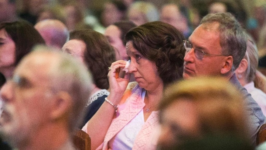 "A woman wipes away tears during a church service at Our Lady of Fatima Catholic church to remember and honor the victims of a deadly shooting at the Grand 16 theater, Sunday, July 26, 2015, in Lafayette, La. John Russell Houser fired on the audience with a semi-automatic handgun about 20 minutes into Thursday night's showing of ""Trainwreck"", killing at least two people and wounding nine with a semi-automatic handgun. (AP Photo/Brynn Anderson)"