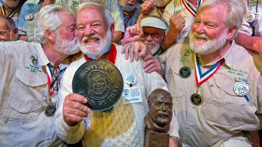 "In this Saturday, July 25, 2015 photo provided by the Florida Keys News Bureau, Charlie Boice, center, is congratulated by previous victors  after winning the 2015 ""Papa"" Hemingway Look-Alike Contest at Sloppy Joe's Bar in Key West, Fla. Boice finally won the contest after trying for 15 years, beating out 121 other entrants following two preliminary rounds, a semi-final and two final rounds. The competition was a facet of the island's annual Hemingway Days festival that ends Sunday, July 26. Planting a playful snook on Boice is Wally Cox, left, the 2014 winner. (Andy Newman/Florida Keys News Bureau via AP)"