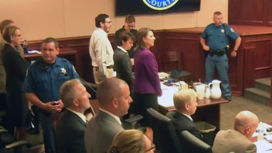 In this image taken from Colorado Judicial Department video, Colorado theater shooter James Holmes, center left, stands for the entrance of the jury, inside Arapahoe County District Court, where his trial continued Thursday, July 23, 2015, in Centennial, Colo. The afternoon saw the conclusion of part one of the penalty phase of the trial of Holmes, with the judge reading the jury's decision that Holmes is eligible for the death penalty. (Colorado Judicial Department via AP, Pool)