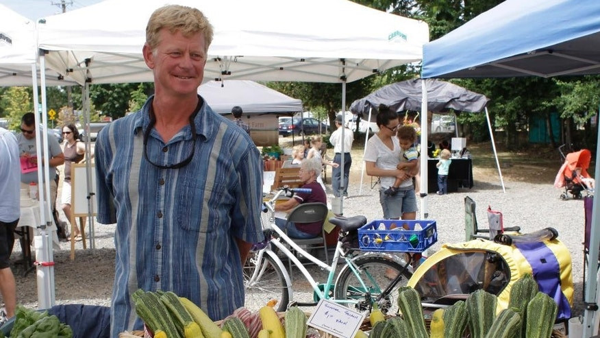 In this Sunday, July 12, 2015 photo, urban farmer Richard Dickinson sells vegetables at the Lent's International Farmers Market in East Portland, Ore. Dickinson, who has lived in East Portland since the 90's and saw first-hand the impact of unfettered growth and the city's neglect, started the Outer Southeast Farmer Training Project with local nonprofit Zenger Farm which teaches East Portlanders how to grow food in their backyards. (AP Photo/Gosia Wozniacka)