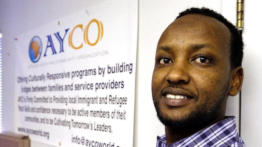 In this Tuesday, July 21, 2015 photo, Somali immigrant leader Jamal Dar, who arrived in the U.S. two decades ago from Kenya, poses for a photo next to the mission statement for AYCO in East Portland, Ore. Dar, worried about new Somali refugees streaming into the state, many of whom were being placed by resettlement agencies in East Portland's cheap apartment complexes, started African Youth and Community Organization in 2009 to help Somali youths but has expanded it to also focus on  family needs. (AP Photo/Don Ryan)