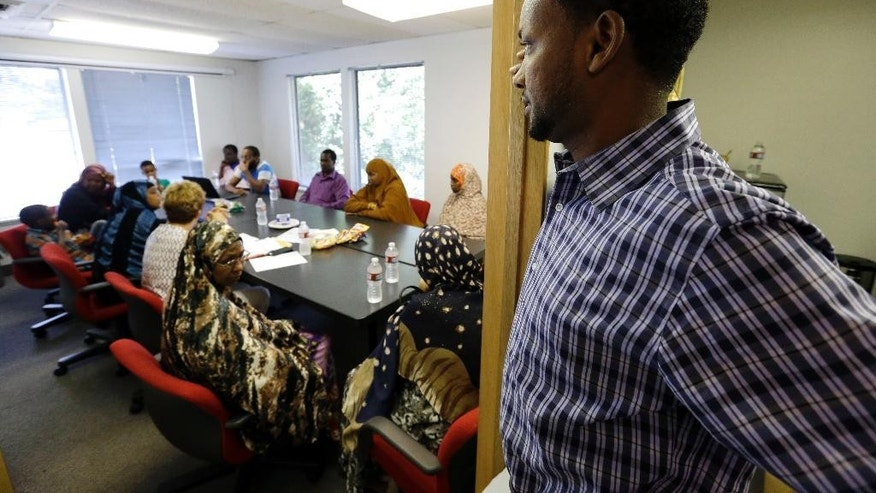 In this Tuesday, July 21, 2015 photo, Somali immigrant leader Jamal Dar, who arrived in the U.S. two decades ago from Kenya, looks in on a community engagement and civic language class for former Somali residents at AYCO offices in East Portland, Ore. Dar, worried about new Somali refugees streaming into the state, many of whom were being placed by resettlement agencies in East Portland's cheap apartment complexes, started African Youth and Community Organization in 2009 to help Somali youths but has expanded it to also focus on  family needs. (AP Photo/Don Ryan)