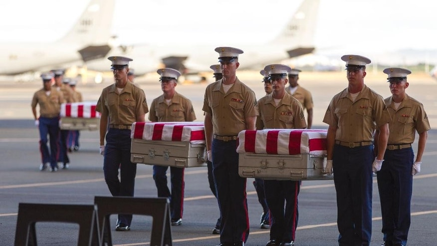 U.S. Marines carry the remains of 36 unidentified Marines found at a World War II battlefield during a ceremony at Joint Base Pearl Harbor-Hickam, Sunday, July 26, 2015, in Honolulu. A Florida-based private organization called History Flight recovered the remains from the remote Pacific atoll of Tarawa. (AP Photo/Marco Garcia)