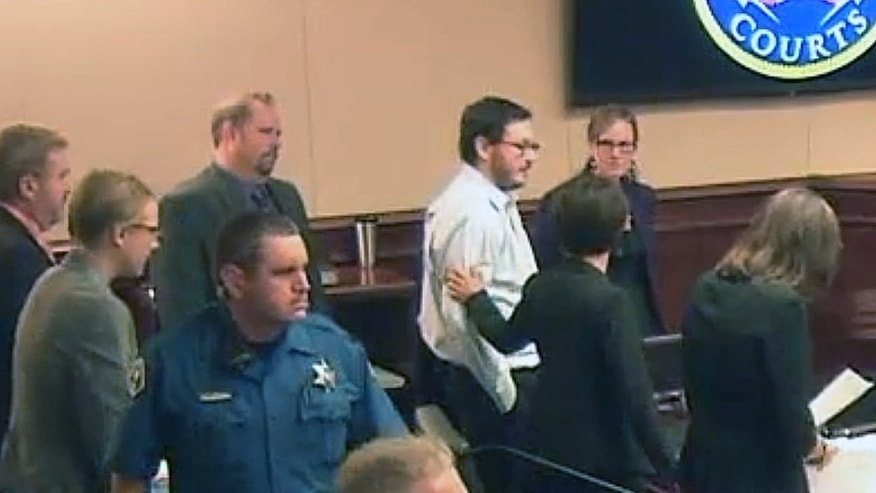 James Holmes, top fourth from right in light-colored shirt, gets a pat on the arm from a member of his defense team following testimony from Holmes' younger sister Chris.