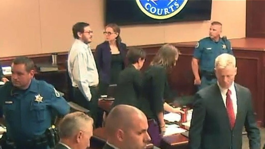 In this image taken from Colorado Judicial Department video, Colorado theater shooter James Holmes, top second from left in light-colored shirt, stands in court during the penalty phase of Holmes' trial, Monday, July 27, 2015, in Centennial, Colo. Dr. Jeffrey Metzner, the court-appointed psychiatrist who concluded that James Holmes was legally sane when he attacked a Colorado movie theater, says Holmes' mental illness still is what caused him to kill 12 people and injure 70 others. (Colorado Judicial Department via AP, Pool)