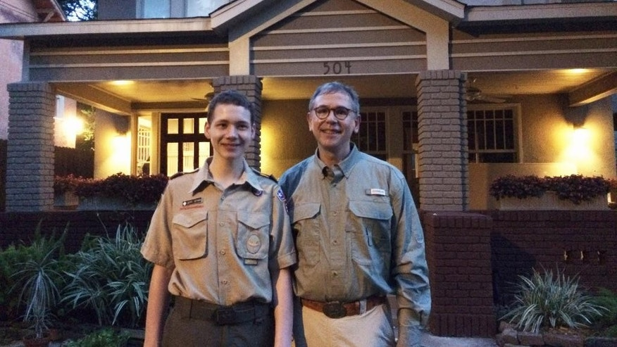 This 2015 photo provided by John S. Adcock shows Jeff Spain and his father Charles Spain in Houston before leaving for Scout summer camp. Charles Spain, a 56-year-old attorney, had not worn a Scout uniform since his post-college years as an in-the-closet Scout employee before he entered law school. On Tuesday morning, July 28, 2015, he registered as an adult leader with the local Scout troop that his 13-year-old son belongs to. (John S. Adcock via AP)
