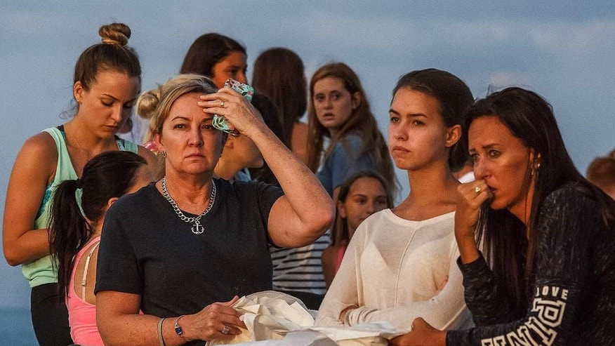 People gather during a candlelight vigil and paper balloon release at Jupiter Inlet Park, Monday, July 27, 2015, for teenagers Austin Stephanos and Perry Cohen in Jupiter, Fla.