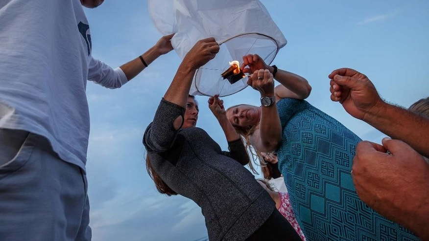 Drew Mydock, from left, Heather Popi and Kristen Murgio light the first paper balloon during a candlelight vigil and paper balloon release at Jupiter Inlet Park, Monday, July 27, 2015, for teenagers Austin Stephanos and Perry Cohen in Jupiter, Fla. The teens were last seen Friday afternoon buying fuel near Jupiter and were believed to have been heading toward the Bahamas. (Thomas Cordy/The Palm Beach Post via AP)