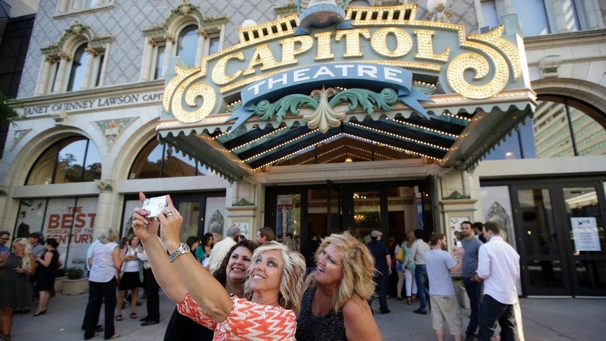 "Brittany Lueders, from left, Diane Orchard and Sue Carter pose for a photograph before entering the Capitol Theatre to see ""The Book of Mormon"" musical Tuesday, July 28, 2015, in Salt Lake City. The biting satirical musical that mocks Mormons has finally come to the heart of Mormonlandia, starting a sold-out, two-week run Tuesday at the Salt Lake City theater two blocks from the church's flagship temple and headquarters. (AP Photo/Rick Bowmer)"