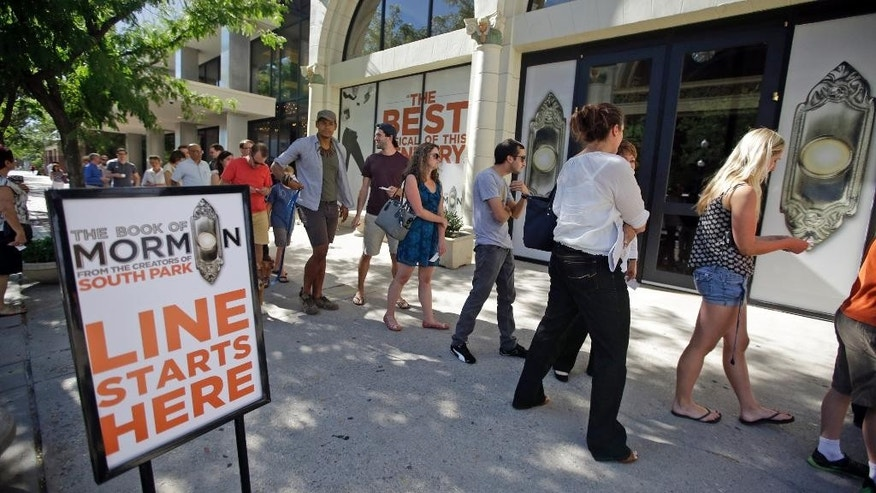 "People wait in line for a lottery drawing for tickets to the ""The Book of Mormon"" at the Capitol Theatre, Tuesday, July 28, 2015, in Salt Lake City. The satirical musical that mocks Mormons has finally come to Salt Lake City, starting a sold-out, two-week run Tuesday at a theater two blocks from the church's flagship temple and headquarters. (AP Photo/Rick Bowmer)"