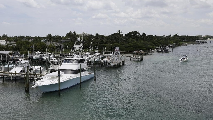 A boat heads out from the JIB Club Marina down the Indian River, Tuesday, July 28, 2015, in Tequesta, Fla. Two Florida teens who have been missing since Friday, July 24, were last seen fueling their boat at this marina before heading out to fish. The search continues for the boys from the Atlantic waters off Daytona Beach, Fla., north through Savannah, Ga. (AP Photo/Lynne Sladky)