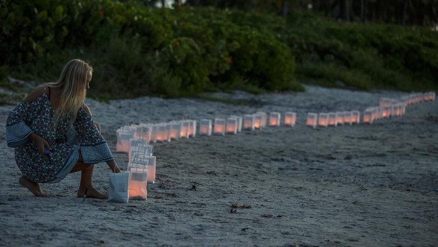 Lilly Folds lights paper lanterns during a candlelight vigil and paper balloon release at Jupiter Inlet Park, Monday, July 27, 2015, for teenagers Austin Stephanos and Perry Cohen in Jupiter, Fla. The teens were last seen Friday afternoon buying fuel near Jupiter and were believed to have been heading toward the Bahamas. (Thomas Cordy/The Palm Beach Post via AP)