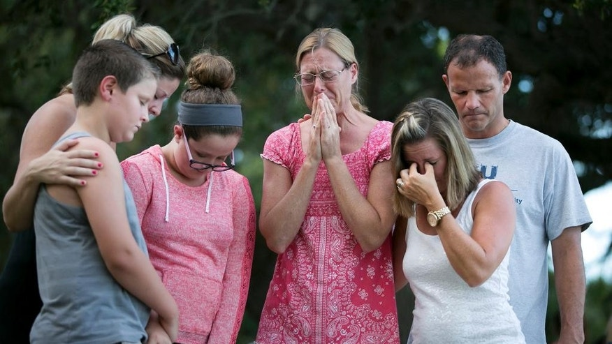 Mary Kaye Hagenbuch, center, says a prayer for Austin Stephanos and Perry Cohen during a prayer vigil at Jupiter Lighthouse Park, Tuesday, July 28, 2015, in Tequesta, Fla. The teenagers have been missing since last Friday when they went out on a boat to go fishing from Tequesta. A search continues for the boys from the Atlantic waters off Daytona Beach, Fla., north through Savannah, Ga. Also pictured are, from left, Hunter Wilkinson, Susan Wilkinson, Lauren Wilkinson, Susie Mydock, second from right, and Rob Hagenbuch (Allen Eyestone/The Palm Beach Post via AP)