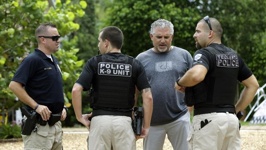 Nick Korniloff, second from right, talks with Tequesta police officers outside of his home Wednesday, July 29, 2015, in Tequesta, Fla. Korniloff is the stepfather of Perry Cohen, one of two teenagers who have been missing since last Friday when they went out on a boat to go fishing from Tequesta, Fla. (AP Photo/Lynne Sladky)