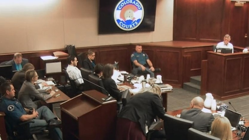 In this image made from Colorado Judicial Department video, Robert Holmes, top second from right, the father of James Holmes, fifth from left in white shirt, gives testimony during the sentencing phase of the Colorado theater shooting trial in Centennial, Colo., on Wednesday, July 29, 2015. Judge Carlos A. Samour Jr. is seen at top right. (Colorado Judicial Department via AP, Pool)
