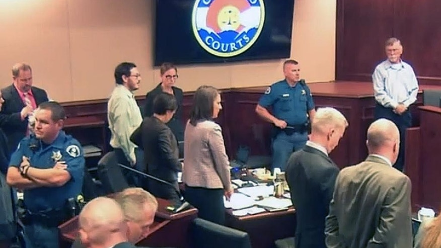 In this image made from Colorado Judicial Department video, Arlene Holmes, top right, the mother of James Holmes, third from left, in white shirt, stand for the jury to leave for a break in testimony during the sentencing phase of the Colorado theater shooting trial in Centennial, Colo., on Wednesday, July 29, 2015. Once they begin deliberating on the sentence, the Holmes jury will be charged with deciding if Holmes is to be executed, or if any mitigating evidence, such as mental health issues, warrants instead life in prison. (Colorado Judicial Department via AP, Pool)