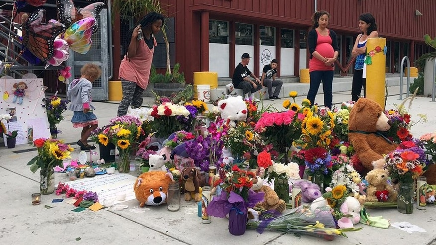 Neighbors look at the growing memorial of flowers, stuffed animals and notes left in memory of Madyson Middleton in Santa Cruz, Calif., Wednesday, July 29, 2015. The close-knit community of artists in Northern California are grieving the death of the 8-year-old girl whose body was found in a trash bin at their housing complex and expressed shock that one of their own, a teenage boy, has been arrested in her death. (AP Photo/Terry Chea)