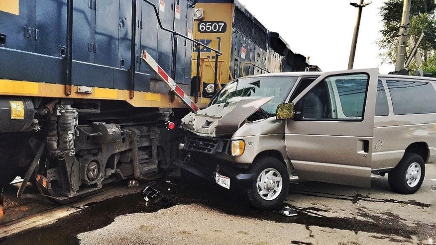 In this Tuesday, July 28, 2015 photo, a van rests against a train engine after a collision in Middletown, Ohio. An adult was killed and 10 others were injured when the van, transporting students to evening vacation Bible school, crashed into the side of the train. The Ohio State Highway Patrol said the gates were down and the warning lights activated at the crossing when the van approached. (Todd Jackson/WHIO-TV) MANDATORY CREDIT.