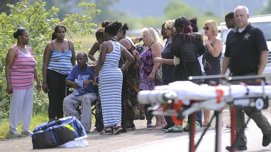 July 28, 2015: Members of St. Jude Family Worship Center gather off the side of the road after their church bus crashed on Interstate 70 in Greenfield, Ind.