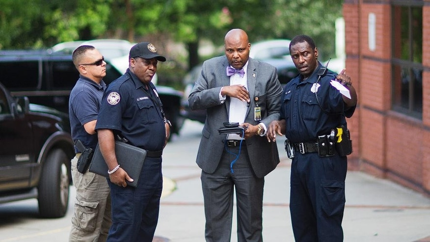 Authorities speak outside Ebenezer Baptist Church where Confederate flags were found Thursday, July 30, 2015, in Atlanta. U.S. authorities are investigating after several Confederate battle flags were discovered near the church and a civil rights center named after Martin Luther King, an iconic leader in the African-American Civil Rights Movement, Thursday morning. (AP Photo/David Goldman)