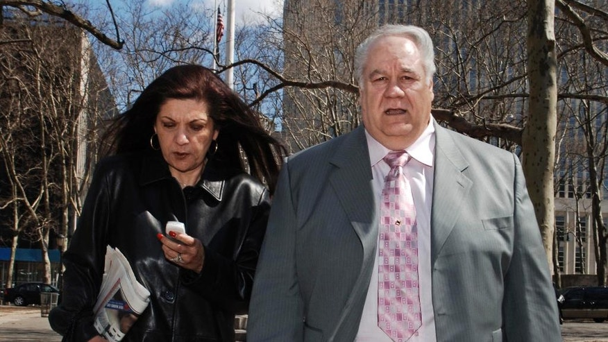 FILE- In this March 22, 2006, file photo, former New York City police detective Louis Eppolito, right, exits Brooklyn federal court with his wife Fran in New York. Lawyers for the family of Israel Greenwald announced the settlement on Thursday, July 30, 2015, in one of the most notorious police corruption cases in city history. The family sued the city in 2006 after Louis Eppolito and Stephen Caracappa were arrested in Las Vegas, where they had retired, and convicted of murder and other crimes. (AP Photo/ Louis Lanzano, File)