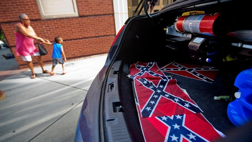 Confederate flags sit in the back of a police car as tourists walk by Ebenezer Baptist Church Thursday, July 30, 2015, in Atlanta. U.S. authorities are investigating after several Confederate battle flags were discovered near the church and a civil rights center named after Martin Luther King, an iconic leader in the African-American Civil Rights Movement, Thursday morning. (AP Photo/David Goldman)