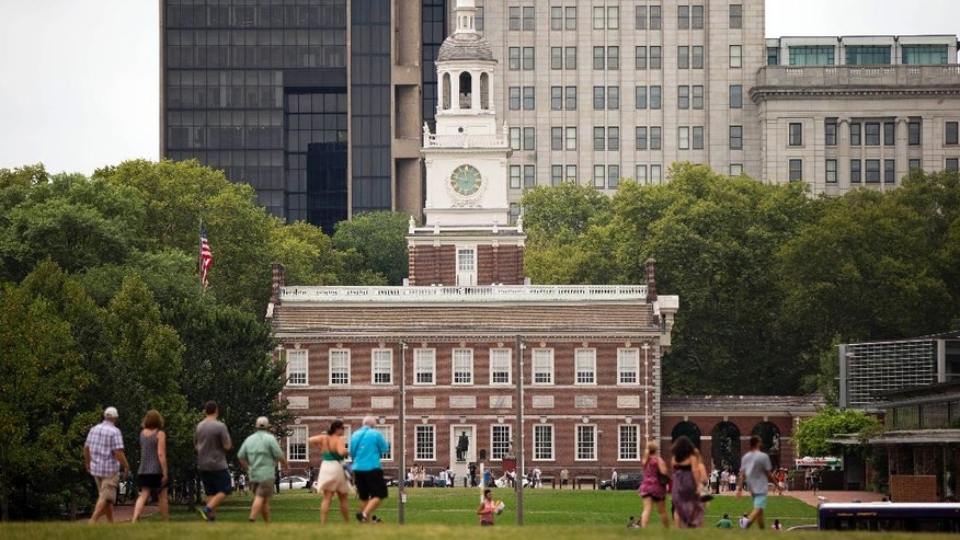 Tourist walk in view of Independence Hall Thursday, July 30, 2015, in Philadelphia.  Pope Francis is scheduled to speak on religious freedom and immigration in the shadow of Independence Hall during his visit to the United States. (AP Photo/Matt Rourke)