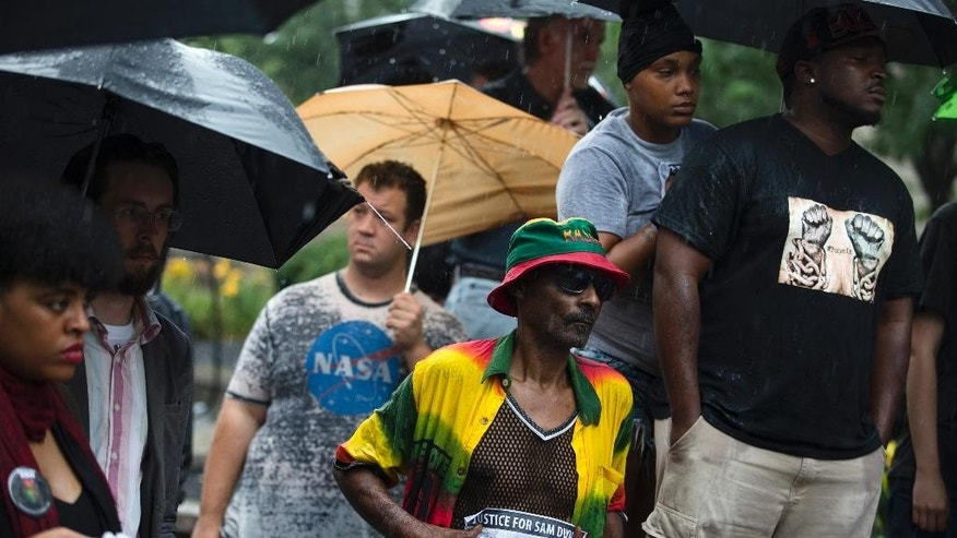 Gee Farrell, center, holds a sign in the rain during a demonstration outside the Hamilton County Courthouse after murder and manslaughter charges against University of Cincinnati Police Officer Ray Tensing were announced for the traffic stop shooting death of motorist Samuel DuBose, Wednesday, July 29, 2015, in Cincinnati. Hamilton County sheriff's spokesman Michael Robison says 25-year-old Tensing turned himself in at the county justice center on Wednesday afternoon. (AP Photo/John Minchillo)