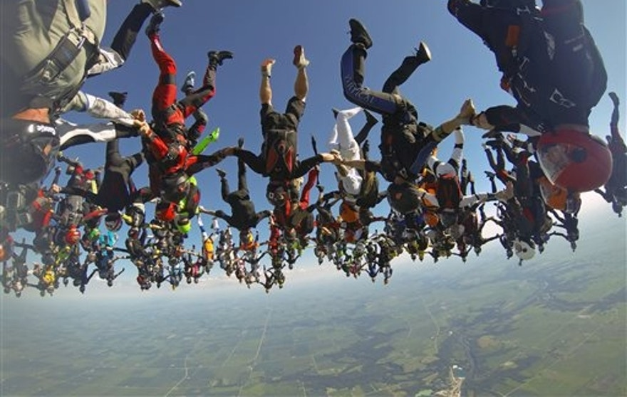 July 31: In this photo provided by Mickey Nuttall, members of an international team of skydivers join hands flying head-down to build their world record skydiving formation over Ottawa, Ill.