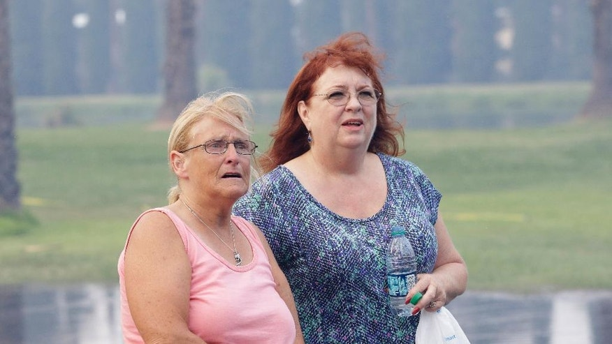 Kim Korth, right, co-owner of Korth's Pirate's, accompanied by her friend, Tracy Holcombe, watch as firefighters battle to save her mobile home,Thursday, July 30, 2015, in Isleton,Calif. Fire crews from multiple agencies battled the fire that destroyed multiple homes and damaged several others. (AP Photo/Rich Pedroncelli)