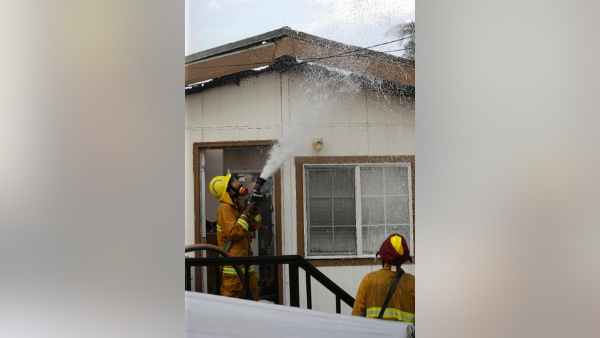 A firefighter puts water on the burning eves of the roof of a mobile home on fire at Korth's Pirate's Lair Marina in Isleton, Calif., Thursday, July 30, 2015. Fire crews from multiple agencies battled the fire that destroyed several homes and damaged others.(AP Photo/Rich Pedroncelli)