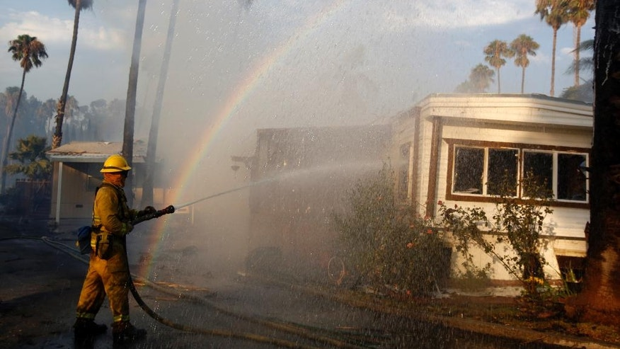 A rainbow emerges from the water sprayed on a burning mobile home at Korth's Pirate's Lair Marina in Isleton, Calif., Thursday, July 30, 2015. Fire crews from multiple agencies battled the fire that destroyed multiple homes and damaged several others. (AP Photo/Rich Pedroncelli)