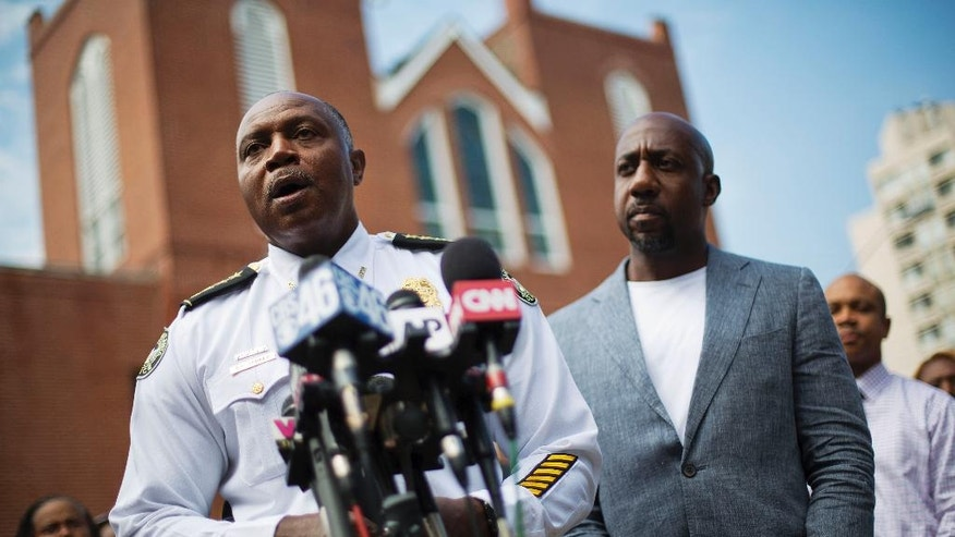Atlanta Police Chief George Turner, left, speaks next to Rev. Raphael G. Warnock, pastor of Ebenezer Baptist Church, during a news conference after Confederate flags were found on the church's premises Thursday, July 30, 2015, in Atlanta. U.S. authorities are investigating after several Confederate battle flags were discovered near the church and a civil rights center named after Martin Luther King, an iconic leader in the African-American Civil Rights Movement, Thursday morning. (AP Photo/David Goldman)