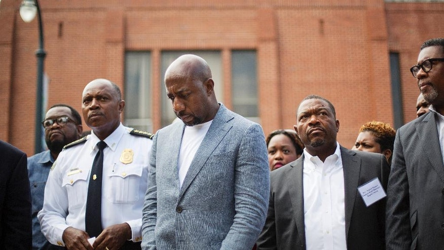 Rev. Raphael G. Warnock, pastor of Ebenezer Baptist Church, center left, waits with Atlanta Police Chief George Turner, left, to speak at a news conference after Confederate flags were found on the church's premises Thursday, July 30, 2015, in Atlanta. U.S. authorities are investigating after several Confederate battle flags were discovered near the church and a civil rights center named after Martin Luther King, an iconic leader in the African-American Civil Rights Movement, Thursday morning. (AP Photo/David Goldman)