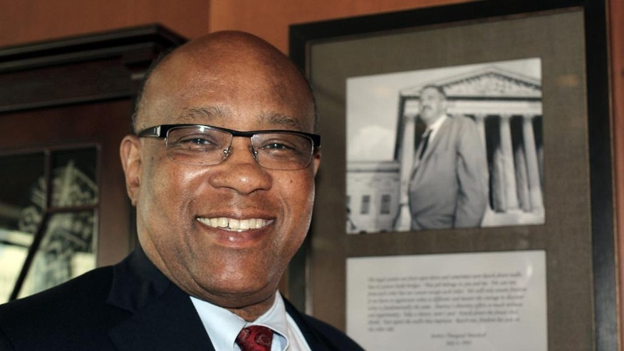 In this photo taken July 8, 2015, U.S. District Judge Michael Davis poses in front of a photo of former Supreme Court Justice Thurgood Marshall in his Minneapolis chambers.  Davis, who became chief judge of the Minnesota district in 2008, and recently stepped down from that post, will turn 68 later this month, but hasn't said whether he'll reduce his caseload. Several men and women have been prosecuted on terror charges in Minnesota since 2009, and all of them have eventually landed in front of Davis. (AP Photo/Jeff Baenen)